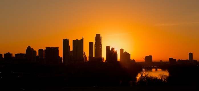 At the moment of sunrise, the eastern sky lights up a brilliant orange over the downtown Austin area. The tallest silhouetted building is the Austoinian. This panorama was captured from the Zilker Park Clubhouse just west of the city.